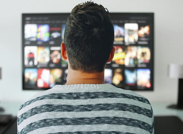 uomo guarda uno spot televisivo